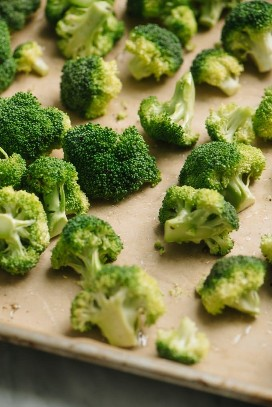 Bite-size broccoli flowers on a baking sheet mixed with olive oil, salt, and pepper.