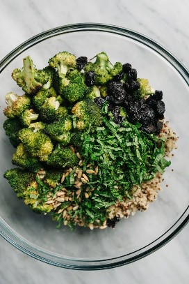 The ingredients for the broccoli and quinoa salad in a glass bowl.