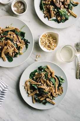 Tres platos de pasta de hongos kale veganos con fideos de trigo integral en una mesa de mármol con copas de vino blanco.