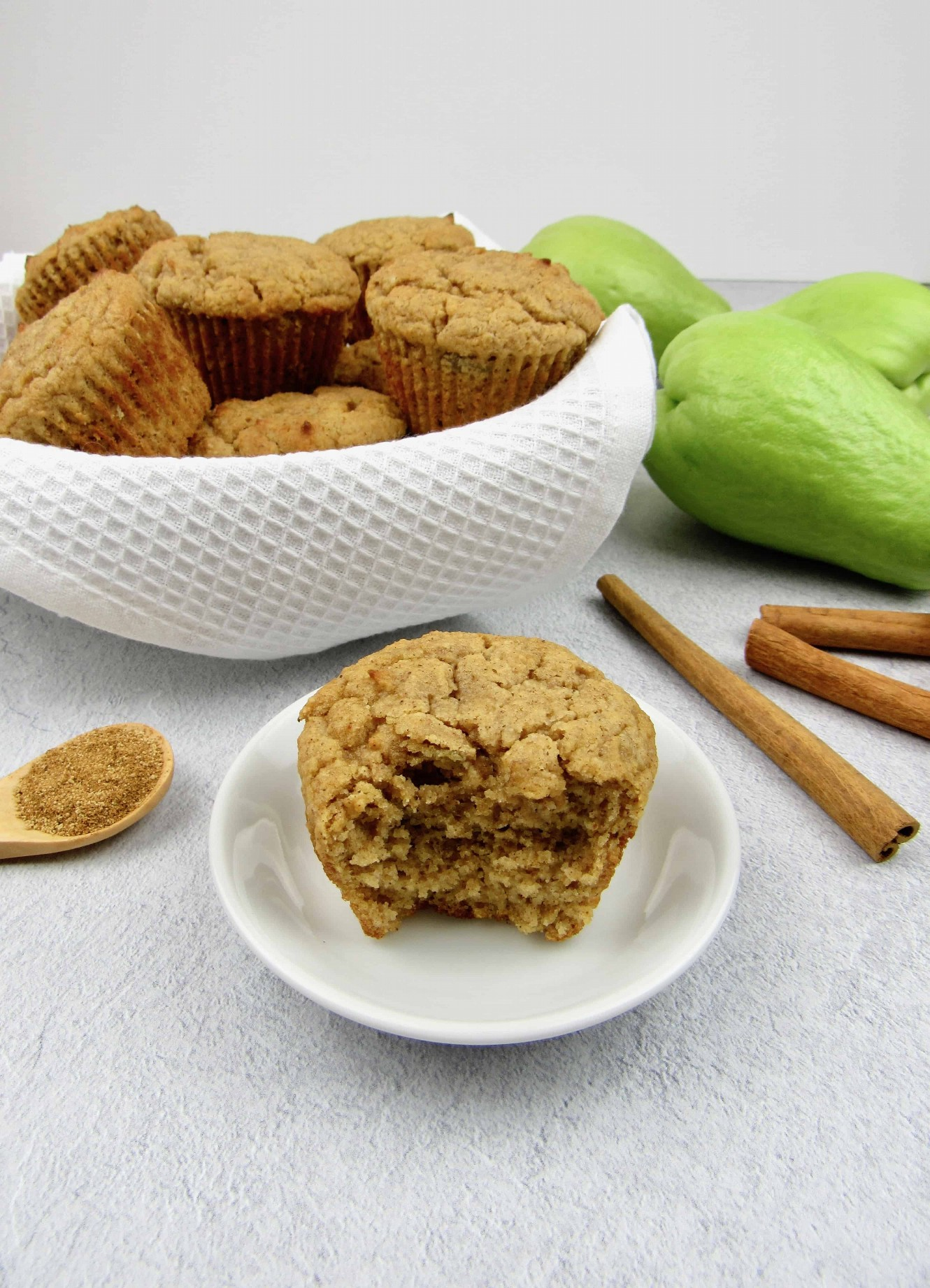 Muffin keto simulacro de manzana con mordisco sacado y canasta con muffins en el fondo