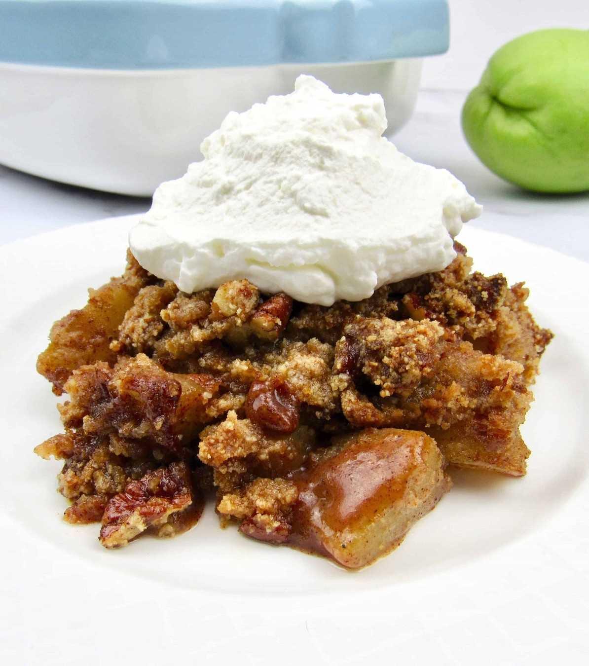 Primer plano de crumble de manzana simulada en un plato blanco con crema batida en la parte superior