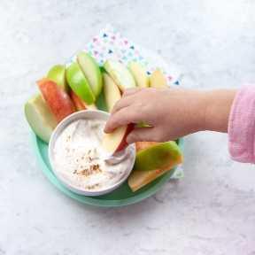 Las manos del niño mojando una manzana en salsa saludable con especias.