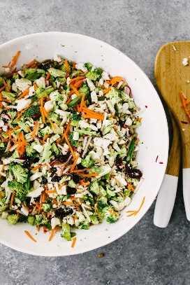 Una vista aérea de una gran ensaladera blanca con los ingredientes mezclados para una ensalada de brócoli y coliflor sobre un fondo de cemento.
