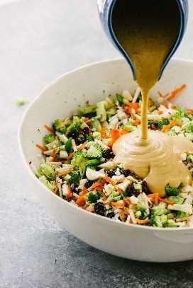 Una pequeña jarra azul vertiendo salsa de mantequilla de sol sobre un todo30 y paleo brócoli y ensalada de coliflor sobre un fondo de cemento.