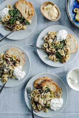 Cuatro platos individuales de primavera pasta primavera servido con un lado de ricotta de limón sobre un fondo azul mantel.
