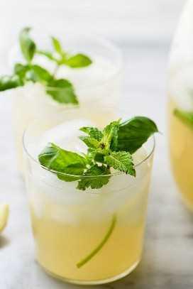 Un vaso de refrescante paleo menta y limonada de albahaca hecha con miel y adornada con hierbas frescas.