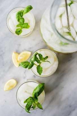 Una jarra de limonada de menta y albahaca con tres vasos llenos de hierbas frescas y rodajas de limón.