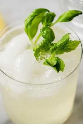 Disparando limonada de menta y albahaca en un vaso con ramitas de hierbas frescas para decorar.