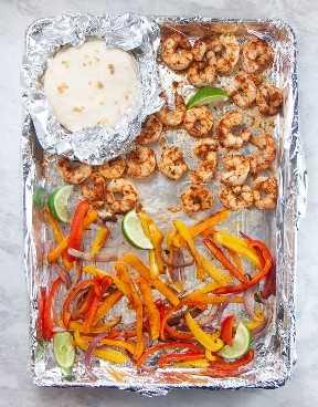 Sartén con tacos de camarones cocidos y tortillas en la parte superior.