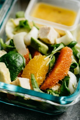 A close up image of food preparation of orange chicken salad with endive, almonds and avocado.