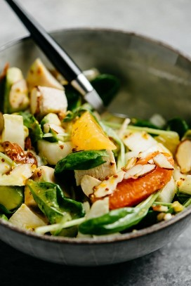 A bowl of orange chicken salad with escarole, almonds and avocado, drizzled with citrus vinaigrette.