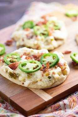¡Jalapeño Popper Dip extendido sobre pan plano! ¡Una merienda tan fácil y probablemente la comida de fútbol más perfecta!