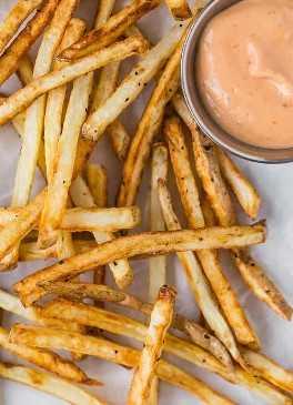 Imagem de batatas fritas com molho.