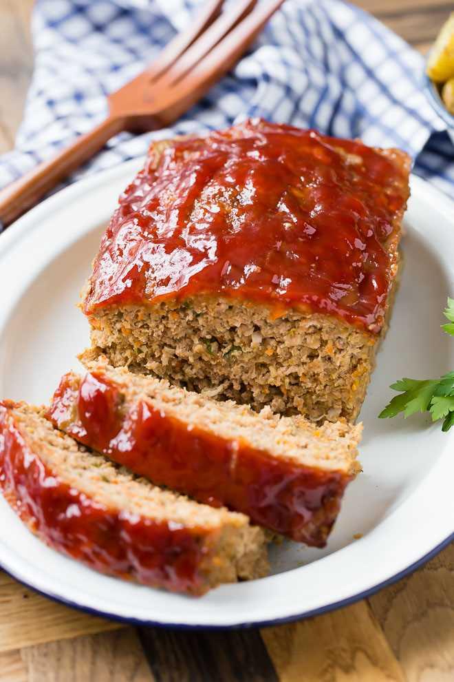 Imagen de pastel de carne húmedo con un glaseado de tomate brillante, cortado en rodajas.