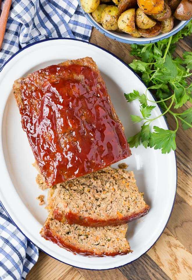 Imagen de un pastel de carne glaseado con tomate tomada desde arriba. También se muestran papas asadas y una ramita de perejil.