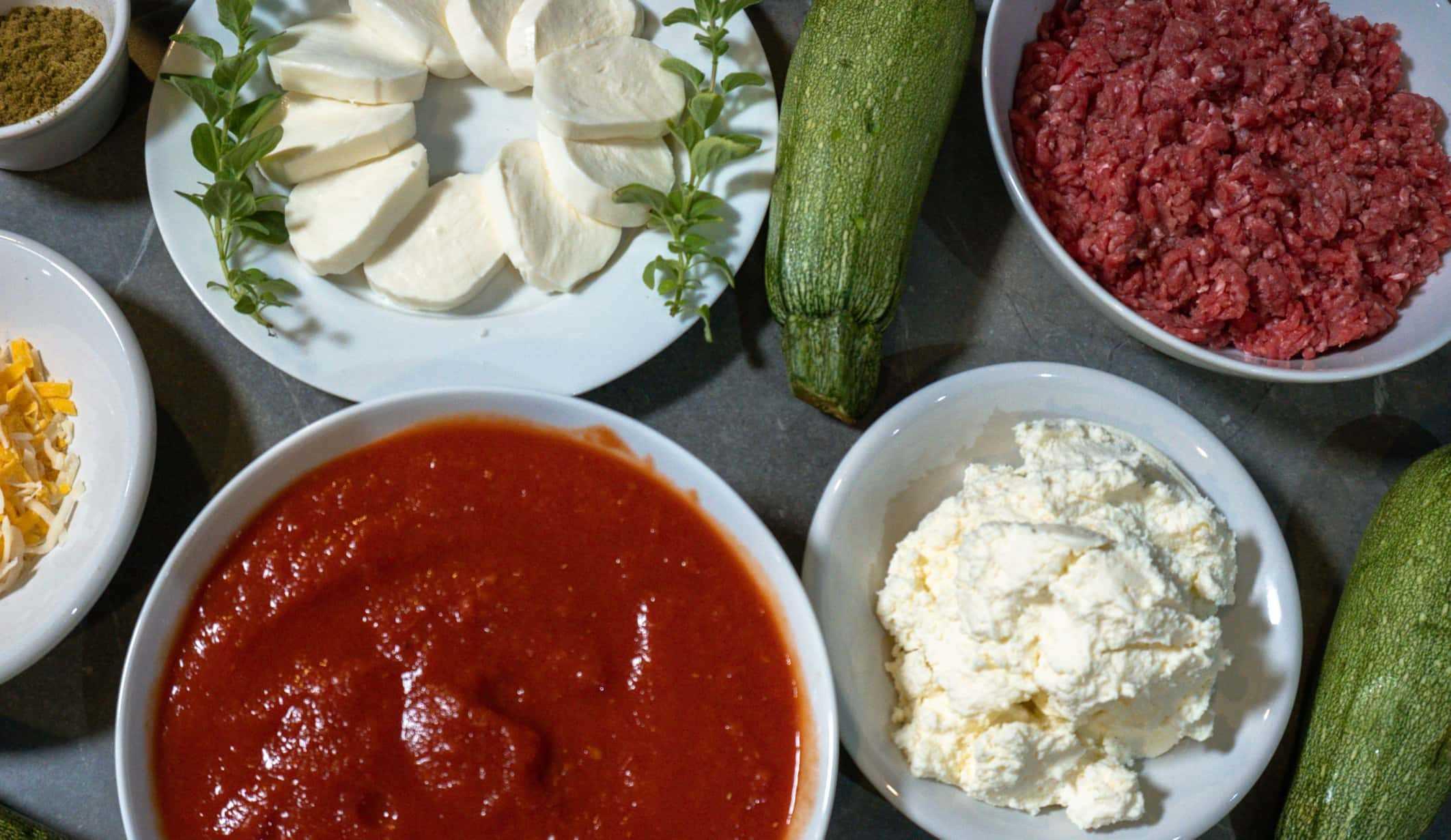 Os ingredientes da lasanha de ceto incluem: orégano, mussarela, abobrinha, carne moída, queijo ralado, tomate esmagado e queijo ricota