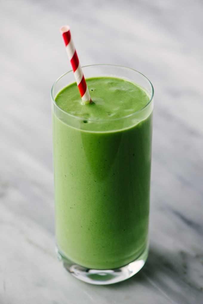 Un batido verde hecho con mango, espinacas, yogur, plátano y miel en un vaso alto con una pajita roja y blanca sobre un fondo de mármol.