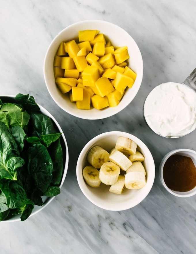 ¡Cómo hacer mi batido de espinacas y mango favorito! Pequeños cuencos de mango cortado en cubitos, espinacas maduras, rodajas de plátano, yogur de Siggi y miel cruda sobre un fondo de mármol.