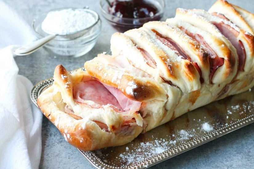 Este Pão Pull Apart Monte Cristo está cheio de carnes saborosas e queijo derretido. É coberto com uma camada de açúcar em pó e servido com framboesa em lata. Funciona muito bem como café da manhã, almoço, jantar ou lanche!