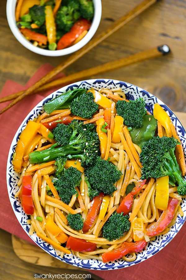 Mexa rápido chinês frite com legumes servidos em uma tigela com pauzinhos. O saboroso vegetal Lo Mein de 15 minutos é servido como um enfeite asiático ou como uma receita saudável para um jantar chinês.