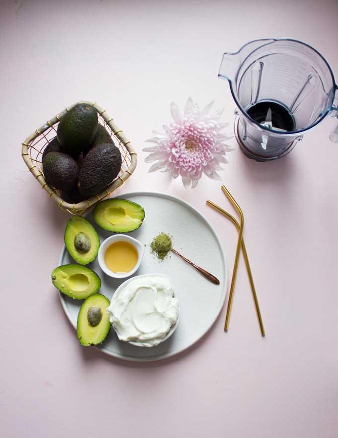 Um prato com um copo de iogurte, alguns abacates cortados ao meio, um pouco de mel, uma colher de chá de matcha e um liquidificador.