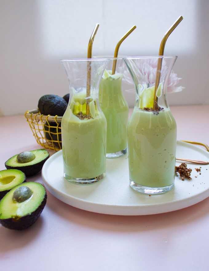 3 copos de smoothies de abacate com canudos dourados num prato branco