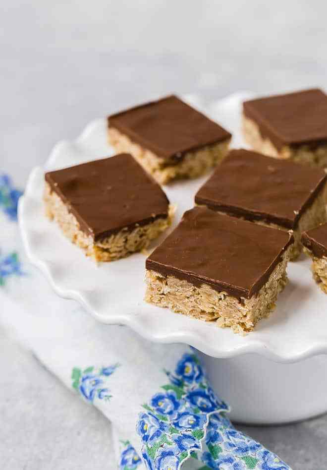 Imagen de barras en un plato, avena crujiente y base de azúcar, cubierto con chocolate cremoso mezclado con mantequilla de maní o mantequilla de semilla de girasol.