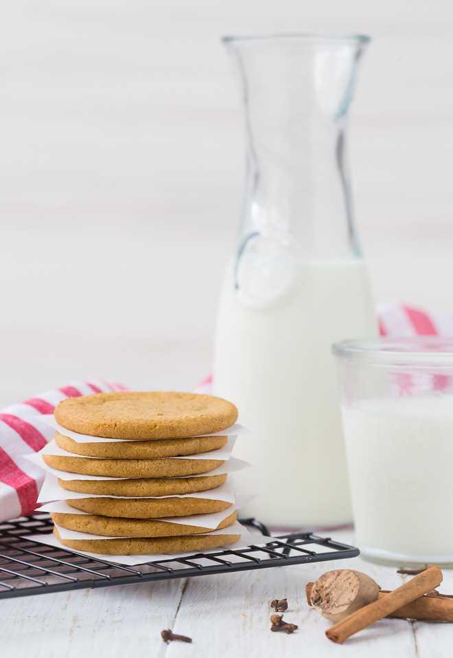 Imagen de una pila de galletas de molino de viento delante de una jarra de leche. Especias enteras (nuez moscada, canela y clavo) representadas en primer plano.