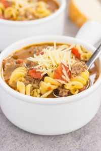 una cuchara cavando en un tazón blanco de sopa de lasaña
