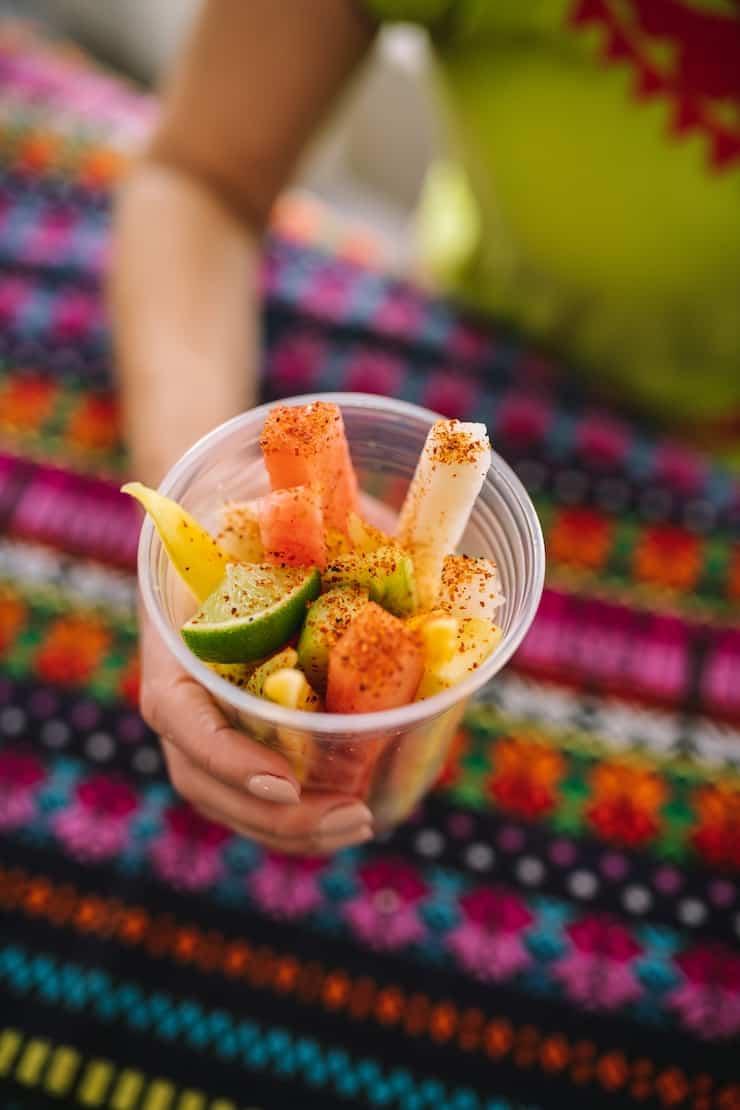 sosteniendo una taza de fruta mexicana en un colorido textil