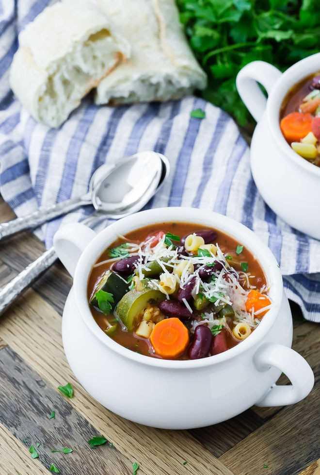 Imagem de sopa minestrone saudável em uma tigela branca com outra tigela no fundo, bem como pão, salsa e duas colheres.