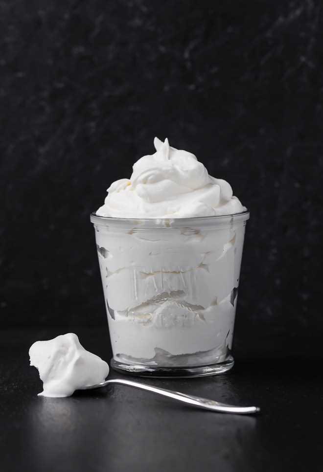 Imagen de crema batida recién batida en un vaso. Una cucharada de crema batida se encuentra en la superficie al lado. Fotografía tomada sobre un fondo negro.