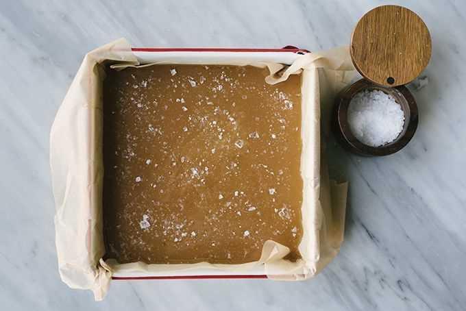 Caramelo dulce en una bandeja para hornear forrada con pergamino, espolvoreado con escamosa sal marina de maldon.