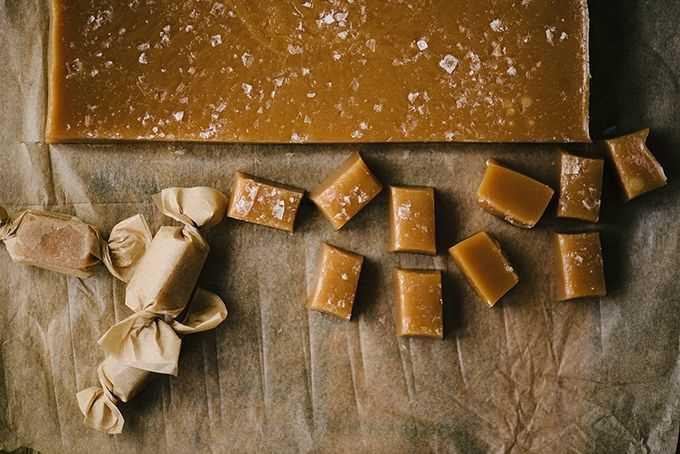 Un bloque de caramelo de caramelo salado casero con pequeños trozos cortados y envueltos en papel pergamino.