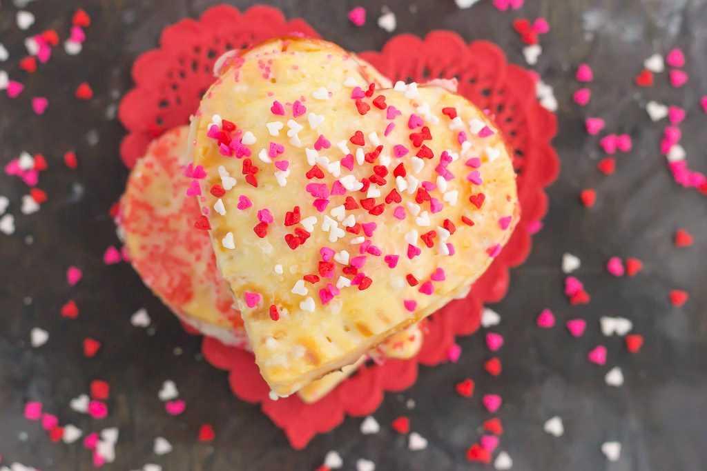 Estas mini empanadas de corazón de fresa son el postre perfecto para consentir a tu amorcito en el día de San Valentín o para entretener a los invitados a la fiesta. Una corteza de pastel prefabricada se corta en forma de corazones y luego se llena con mermelada de fresa dulce. ¡Es un regalo impresionante que lleva mucho tiempo pero es muy fácil de hacer!