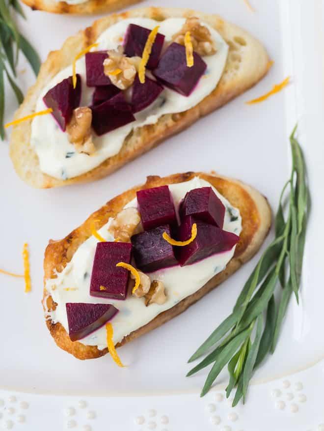 Imagem de beterrabas bonitas e queijo de cabra em cima de bruschetta, guarnecido com nozes e raspas de laranja.