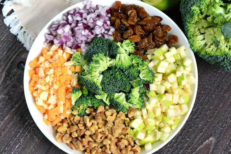 Salada de brócolis. Esta salada de brócolis é feita com maçãs, nozes, passas, migalhas de queijo e cebola vermelha. Uma combinação perfeita para piqueniques, refeições compartilhadas e festas ao ar livre.