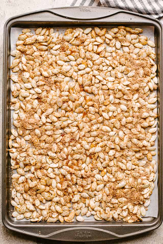 """semillas de calabaza crudas en una bandeja para hornear """"width ="""" 640 """"height ="""" 960 """"data-pin-description ="""" Semillas de calabaza con azúcar y canela - Semillas de calabaza tostadas dulces con una deliciosa cobertura de azúcar con canela. Es el bocadillo perfecto para hacer con las semillas sobrantes de las calabazas navideñas. # calabaza # semillas de calabaza"""