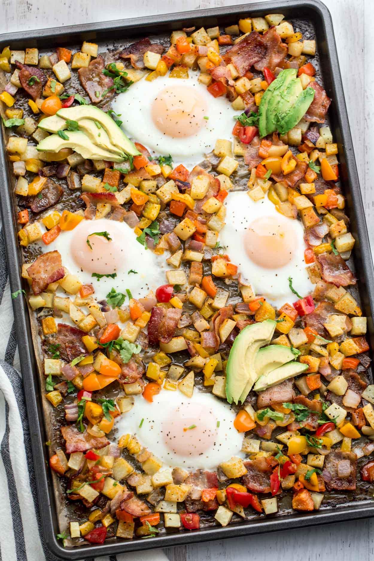 Uma frigideira café da manhã batatas e ovos com legumes e bacon.