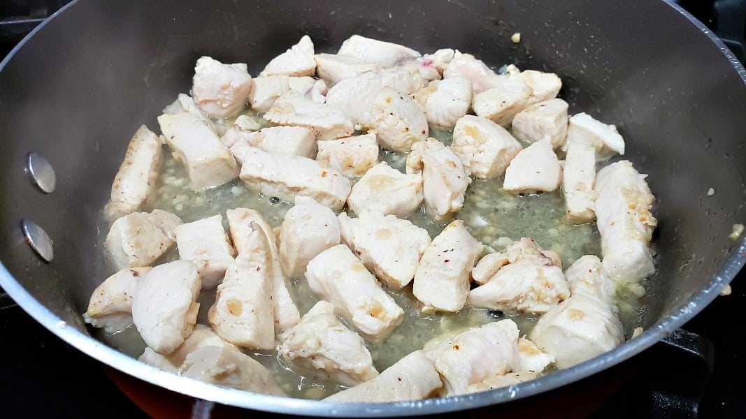 pollo en cubitos y ajo cocinado en una sartén grande