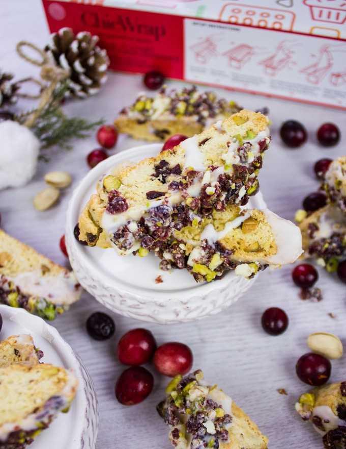 Receita de bolo de pistache e mirtilo mergulhada em chocolate branco e polvilhada com mirtilos e pistache