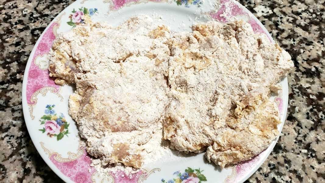 dois pedaços de frango revestidos com misturas de farinha de ovo