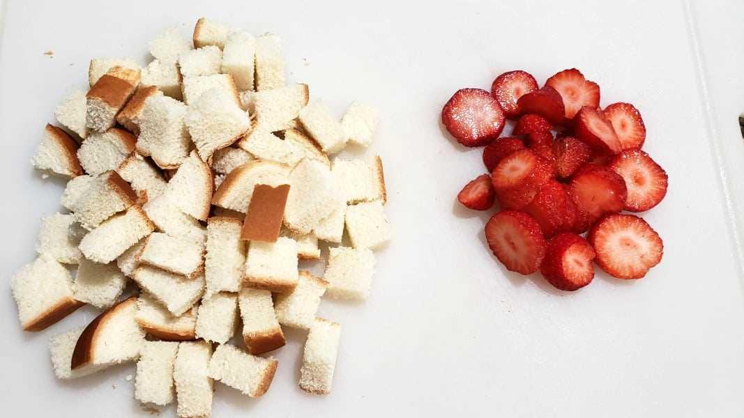 """morangos fatiados e pão em cubos """"srcset ="""" https://gamecookingpasteleria.org/wp-content/uploads/2020/02/1582835044_929_Receta-de-pudin-de-pan-con-fresas-y-crema-para.jpg 1067w, https://cdn1.zonacooks.com/wp-content/uploads/2018/08/Strawberries-and-Cream-Bread-Pudding-Recipe-for-Two-1-500x281.jpg 500w """"tamanhos ="""" (largura máximo: 1067px) 100vw, 1067px"""
