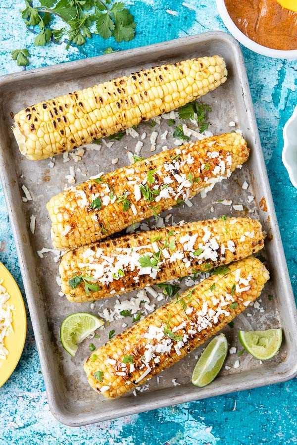 Elote de maíz mexicano a la parrilla sobre una bandeja para hornear de metal con rodajas de limón