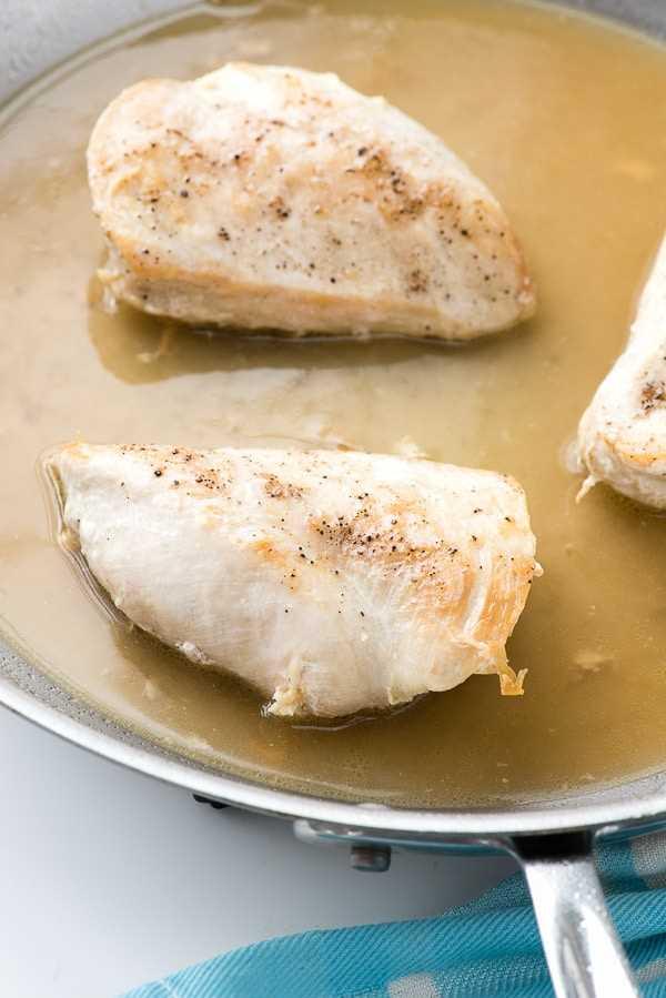 peitos de frango desossados e úmidos, cozidos em uma frigideira grande de alumínio