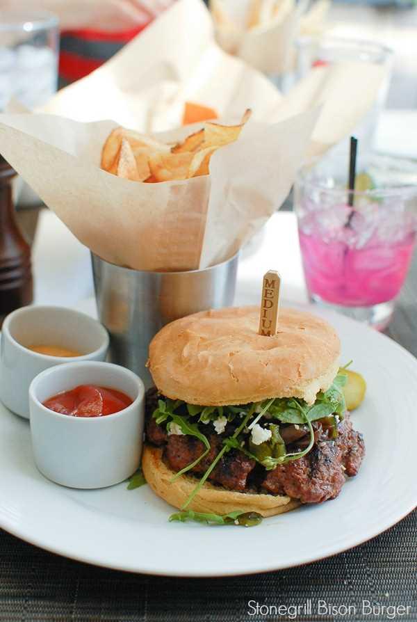 plato blanco con una hamburguesa de bisonte, papas fritas y 2 condimentos con salsa de tomate y mostaza