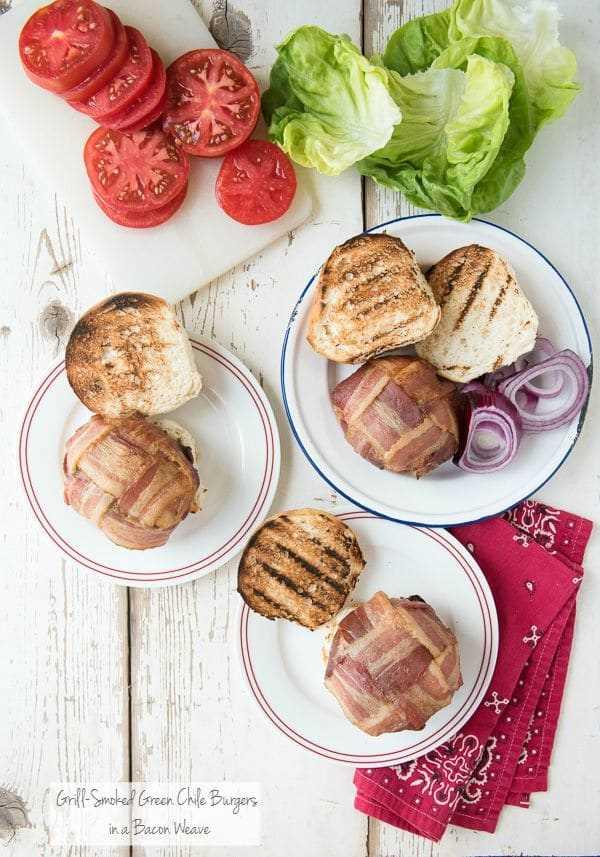 3 platos blancos con hamburguesas de chile verde ahumado a la parrilla con tejido de tocino rodeado de lechuga fresca y tomates en rodajas