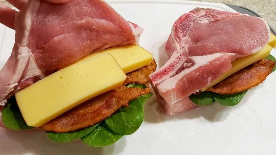 """adicionando duas fatias de gouda defumado nas costeletas de porco """"srcset ="""" https://cdn1.zonacooks.com/wp-content/uploads/2020/02/Smoked-Gouda-and-Bacon-Stuffed-Pork-Chops- Dinner- for-Two-5-900x507.jpg 900w, https://cdn1.zonacooks.com/wp-content/uploads/2020/02/Smoked-Gouda-and-Bacon-Stuffed-Pork-Chops-Dinner-for -Two -5-500x282.jpg 500w, https://cdn1.zonacooks.com/wp-content/uploads/2020/02/Smoked-Gouda-and-Bacon-Stuffed-Pork-Chops-Dinner-for-Two- 5- 768x432.jpg 768w, https://cdn1.zonacooks.com/wp-content/uploads/2020/02/Smoked-Gouda-and-Bacon-Stuffed-Pork-Chops-Dinner-for-Two-5-320x180 .jpg 320w, https://cdn1.zonacooks.com/wp-content/uploads/2020/02/Smoked-Gouda-and-Bacon-Stuffed-Pork-Chops-Dinner-for-Two-5-480x270.jpg 480w https: //cdn1.zonacooks.com/wp-content/uploads/2020/02/Smoked-Gouda-and-Bacon-Stuffed-Pork-Chops-Dinner-for-Two-5-720x405.jpg 720w, https: // cdn1.zonacooks.com/wp-content/uploads/2020/02/Smoked-Gouda-and-Bacon-Stuffed-Pork-Chops-Dinner-for-Two-5-735x414.jp g 735w, https: //cdn1.zonac ooks.com/wp-content/uploads/2020/02/Smoked-Gouda-and-Bacon-Stuffed-Pork-Chork-Chops-Dinner-for-Two-5.jpg 1000w """"tamanhos = """"(largura máxima: 900px) 100vw 900px"""