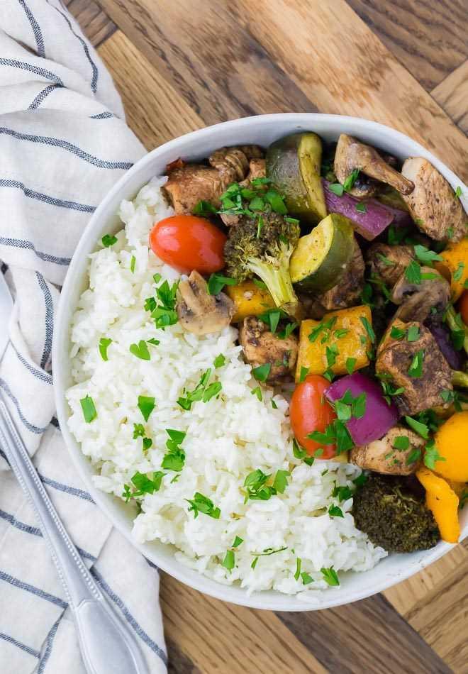 Imagem de uma panela com mel de frango balsâmico e legumes (tomate, pimentão, brócolis, cebola, cogumelos), servido com arroz e guarnecido com salsa.