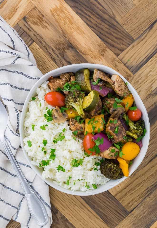 Uma tigela branca cheia de arroz, frango e legumes.